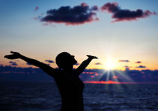Woman silhouette over sunset Stock Image
