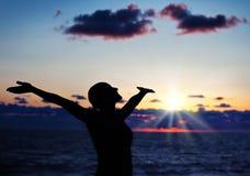Woman silhouette over sunset. Sky, dark black shadow of female body with hands up, teenage girl having fun outdoor, enjoying sundown on the beach, freedom Stock Image