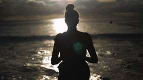 Woman silhouette over sunset sky, black shadow of female body with hands up. Young beautiful woman standing towards the sun on sea beach during a amazing sunset stock video