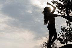 Woman silhouette over sunset sky stock photo