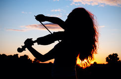 Woman silhouette playing violin Royalty Free Stock Photos
