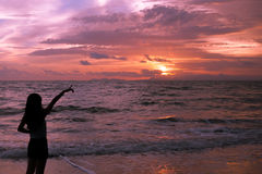 Woman silhouette pointing in the sunset Stock Photos