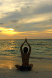 Woman silhouette practicing yoga on the beach Stock Images