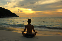 Woman silhouette practicing yoga on the beach Royalty Free Stock Photo