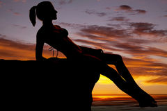 Woman silhouette on rock in sunset Stock Images