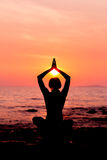 Woman silhouette sitting in lotus position on sea background back lit. Woman silhouette sitting in lotus position on sunset sea background back lit stock image