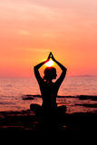 Woman silhouette sitting in lotus position on sea background back lit Royalty Free Stock Images