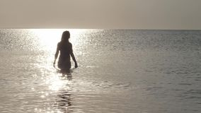 Woman in a bikini standing in the middle of sun road on the seawater Tender waves swaying and play by glitters in rays