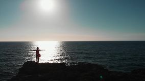 Woman silhouette standing on cliffs with hands apart in air against sun and sun road on blue ocean. Drone view of girl with arms a stock video footage