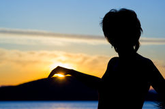 Woman Silhouette at sunset. Woman Silhouette with sun in the hand Royalty Free Stock Images