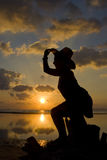 Woman silhouette in the sunset Stock Photos