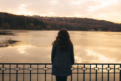 Woman silhouette at sunset lake. Rear view of sad woman silhouette at sunset lake. Female wearing a warm coat staying in cold weather. Loneliness and sadness Royalty Free Stock Photos