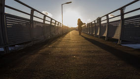 Woman silhouette  in sunset on pedestrian bridge. Perspective Stock Image