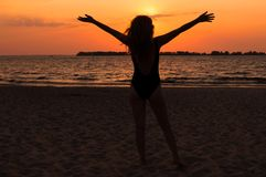 Woman silhouette in swimsuit with flowing hair, raised hands and standing on beach near sea stock image