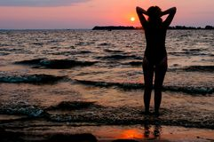 Woman silhouette in swimsuit with raised arms looking at amazing sunrise near sea royalty free stock photo
