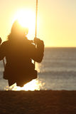 Woman silhouette swinging at sunset on the beach Stock Image