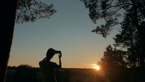 Woman silhouette taking photo of sunset with smartphone stock video footage