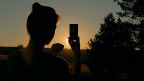 Woman silhouette taking photo of sunset with smartphone stock footage