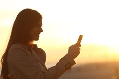 Woman silhouette using a smart phone at sunset Stock Images