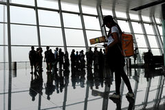 Woman in silhouette walking and waiting in an Airport Royalty Free Stock Images