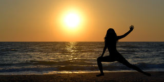 Woman silhouette in a yoga pose on the beach Royalty Free Stock Photo