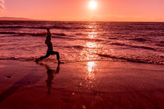Woman Silhouetted Practicing Yoga on Beach Stock Image