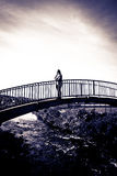 Woman silhouetted strolling on a modern bridge royalty free stock photos
