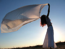 Woman and silk. Woman playing with the wind Royalty Free Stock Image