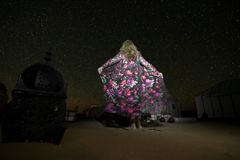A woman in a silk dress looks at starry sky in a campground in the middle of the Erg Chebbi desert stock photography