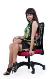 Woman in a silk dress sitting on a chair Royalty Free Stock Images
