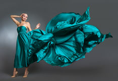 Woman in  silk dress waving on wind. Flying and fluttering gown cloth over gray background Stock Photos