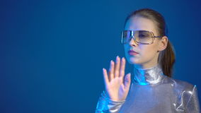Woman in silver clothing turning over the virtual pages. Young woman in silver clothing wearing eyeglasses turning over the virtual pages, over blue background stock video footage