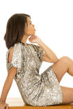 Woman silver dress sit side elbow on knee Stock Image