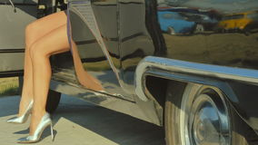 The woman in silver shoes comes out from retro car. The woman opens the door of exclusive automobile. The female in a silver high heels shoes comes out from the stock video