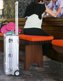 Woman with silver suitcase filling in check in form at hotel Stock Photography