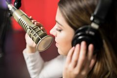 Woman singer face singing in a radio show. Close up of woman singer face singing song on microphone at radio station royalty free stock photos