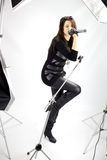 Woman singer getting photo shoot. Rock singer with studio lights for photo shoot stock photography