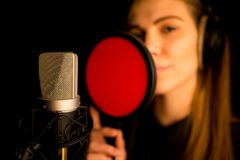 Woman singer with headphones recording in studio. Royalty Free Stock Images