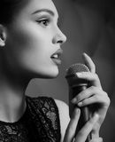 Woman singer with microphone. Beautiful young woman singer with microphone royalty free stock image