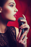Woman singer with microphone. Beautiful young woman singer with microphone stock image