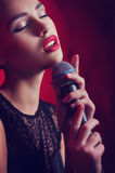 Woman singer with microphone. Beautiful young woman singer with microphone royalty free stock photo