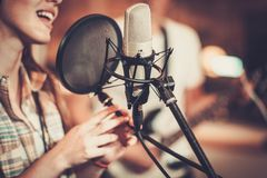Woman singer in a studio. Woman singer in a recording studio Royalty Free Stock Images