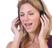 Woman singing. Beautiful woman singing and enjoying music thru headphones royalty free stock photography