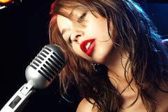 Woman Singing. Into a microphone stock images