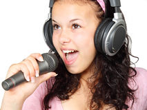Woman singing along. Young woman in pink singing with microphone and headphones royalty free stock image