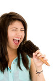 Woman singing into brush Stock Images