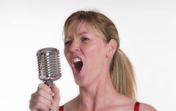Woman singing with a chrome microphone Royalty Free Stock Photo