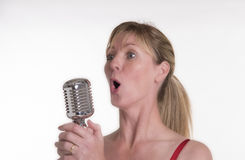 Woman singing with a chrome microphone Stock Image