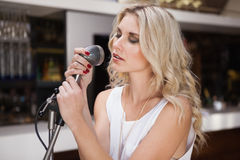 Woman singing while closing her eyes Royalty Free Stock Images
