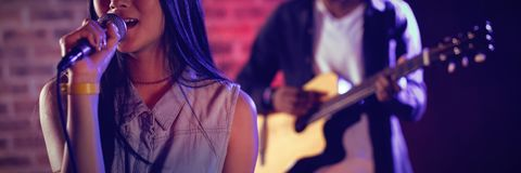 Woman singing by guitarist at club. Young women singing by male guitarist at nightclub Stock Image